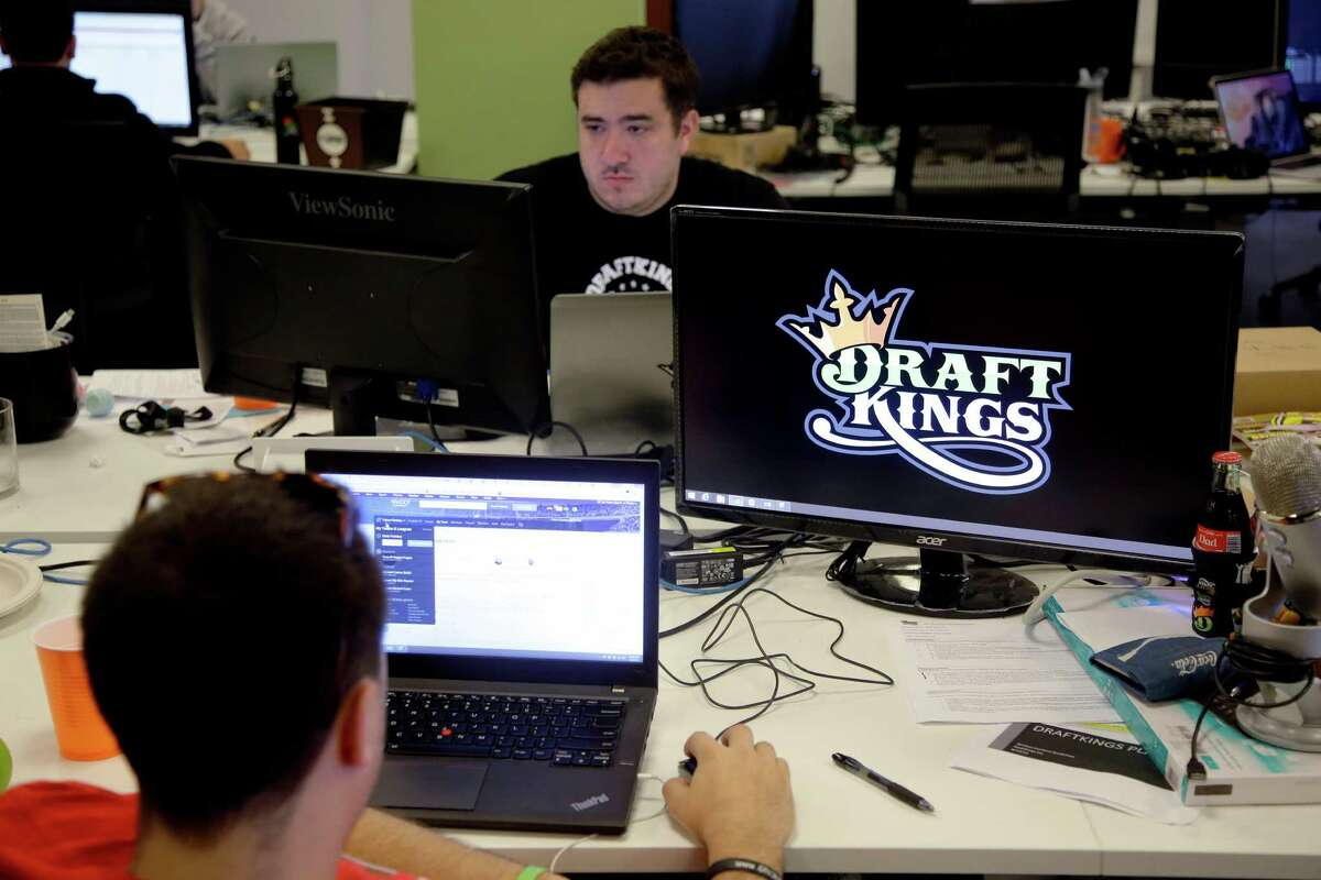 In this Sept. 9, 2015, file photo, Len Don Diego, marketing manager for content at DraftKings, a daily fantasy sports company, works at his station at the company's offices in Boston. The daily fantasy sports industry is eyeing a breakout season as NFL games begin. And its two dominant companies, DraftKings and FanDuel, are touting lucrative opening week prizes to try to draw more customers as more competitors pop up. (AP Photo/Stephan Savoia, File)