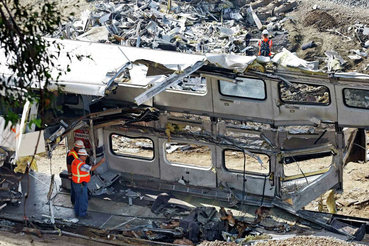 File - This Sept. 14, 2008 file photo shows investigators photographing the mangled inside of a Metrolink commuter train in Chatsworth, Calif. Despite a rash of deadly train crashes, the railroad industry?'s allies in Congress are trying to push back the deadline for installing technology to prevent the most catastrophic types of collisions to at least 2020, half a century after accident investigators first called for such safety measures. (AP Photo/Richard Vogel, File) ORG XMIT: WX102