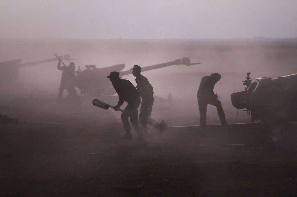 In this photo taken on Wednesday, Oct. 7, 2015, Syrian army personnel load howitzers near the village of Morek in Syria. The Syrian army has launched an offensive this week in central and northwestern Syria aided by Russian airstrikes. (AP Photo/Alexander Kots, Komsomolskaya Pravda, Photo via AP) ORG XMIT: MOSB105