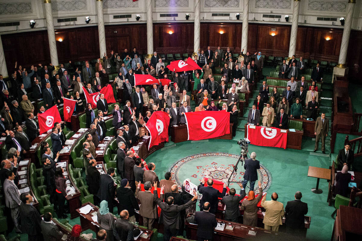 FILE - In this Sunday, Jan. 26, 2014 file photo, members of the Tunisian National Constituent Assembly celebrate the adoption of the new constitution in Tunis, Tunisia. A Tunisian democracy group won the Nobel Peace Prize on Friday for its contributions to the first and most successful Arab Spring movement. The Norwegian Nobel Committee cited the Tunisian National Dialogue Quartet
