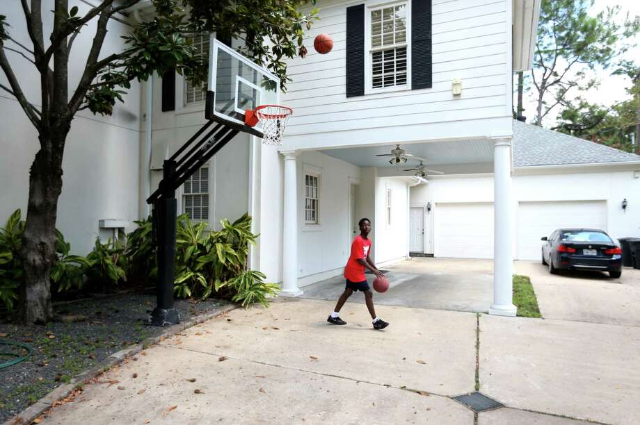 Johnathan shoots baskets with Mason. Photo: Gary Coronado, Houston Chronicle / © 2015 Houston Chronicle