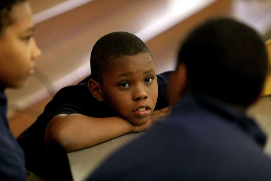 "Jarvis Cormier, 11, a fifth-grader, waits for his ""Shepherd"" mentors, Travis and Paige Robinson, during lunch break at Yellowstone Academy. Photo: Gary Coronado, Houston Chronicle / © 2015 Houston Chronicle"