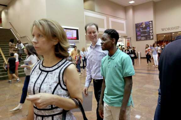 "Church member John Meredith, along with wife Shirley, left, ""Shepherd"" mentors to Johnathan Gooden, 14, an eighth-grader at Yellowstone Academy, leave Second Baptist Church after attending a service Sunday, Sept. 20, 2015, in Houston, Texas. Johnathan sometimes spends the weekend with the Merediths attending Second Baptist Church. Shepherd-A-Child is a one-on-one mentoring program where students of Yellowstone are matched up with volunteers to guide them in area of their lives."