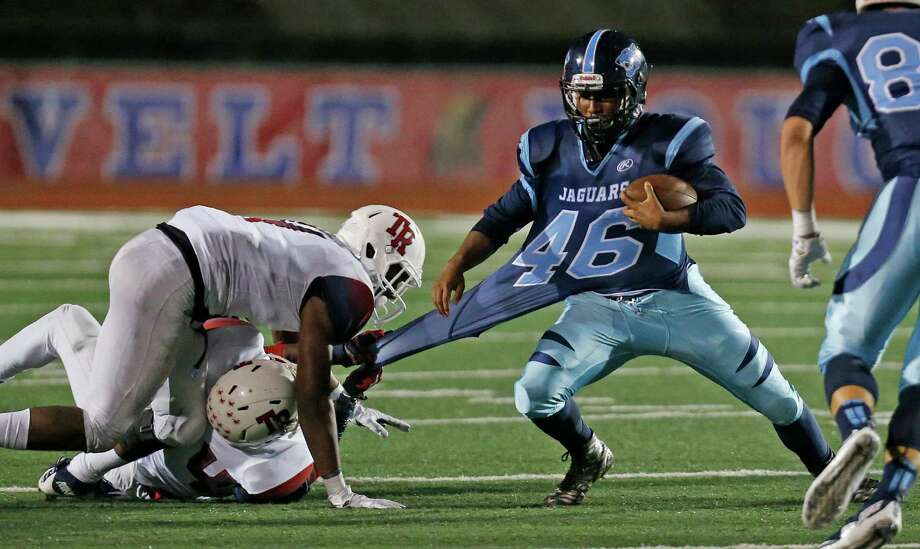 Roosevelt's Elijah Hunter holds onto the jersey of Johnson's Anthony Hendrix on a run in the second quarter of a District 26-6A high school football game at Comalander Stadium on Oct. 9, 2015. Photo: Ron Cortes /Express-News