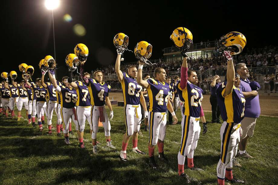 Above: Middletown players raise their helmets at the end of the national anthem.   Left: Fans show support for their town and team. Photo: Michael Macor, The Chronicle