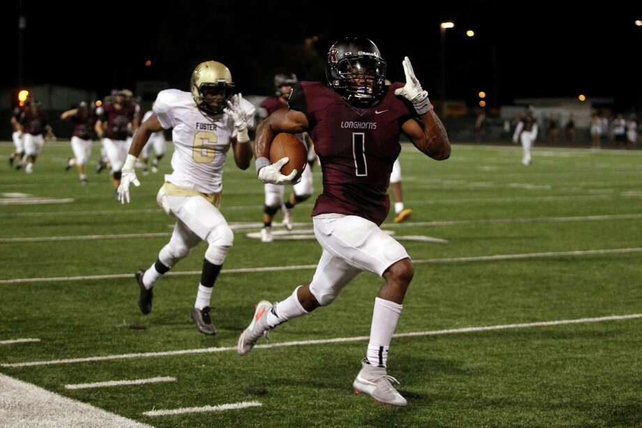 George Ranch's Darius Anderson, right, wins the race to the end zone with less than four minutes left in Friday night's game at Traylor Stadium. His 71-yard touchdown run provided just enough cushion to beat District 24-5A rival Foster. Photo: J. Patric Schneider, Freelance / © 2015 Houston Chronicle