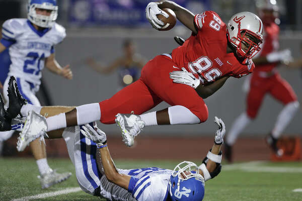 Rocket receiver Rashad Beecham flies over Unicorn defender Dillon Hanson after a catch in the second quarter as Judson hosts New Braunfels at Rutledge Stadium on October 9, 2015.