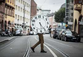 Younus Bouaoun, one of the few watch maker apprentices in Frankfurt, carries a large wall clock across a street in Frankurt, central Germany, Friday,  Oct. 9, 2015. (Frank Rumpenhorst/dpa via AP)