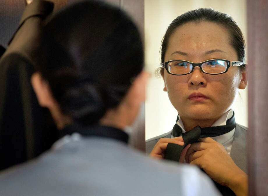Chinese butler school graduate Zhang Zhejing gets her necktie just right as she prepares for a day of butler duties at a conference in Beijing. Photo: Mark Schiefelbein, STF / AP