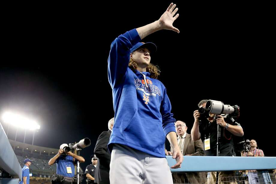 Jacob deGrom waves to fans as he leaves the field after equaling a Mets playoff record set by Tom Seaver in 1973. Photo: Stephen Dunn, Getty Images