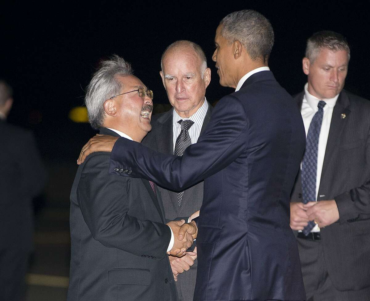 President Barack Obama, right front, is greeted on the tarmac by California Gov. Jerry Brown, center, and San Francisco Mayor Ed Lee, left, upon his arrival at San Francisco International Airport, Friday, Oct. 9, 2015, in San Francisco.