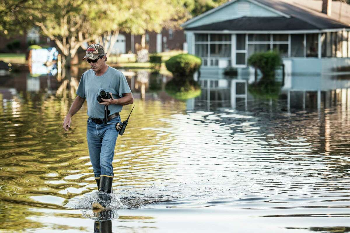 EUTAWVILLE, SC - OCTOBER 8: Lieutenant Woody Benton, of the Eutawville Fire Department wades through floodwater 2015 in Eutawville, South Carolina. The state of South Carolina experienced record rainfall amounts over the weekend and officials expect the costs to be in the billions. (Photo by Sean Rayford/Getty Images) ORG XMIT: 583062459