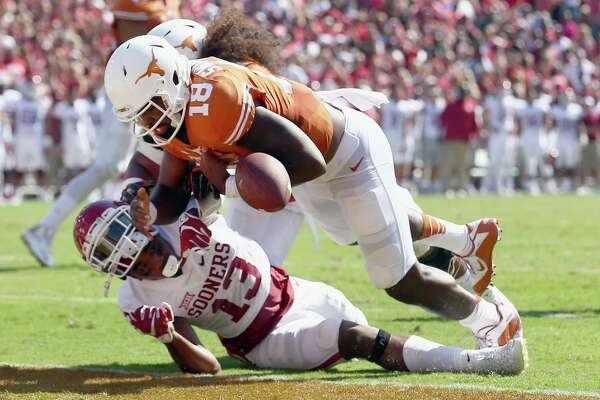 DALLAS, TX - OCTOBER 10:  Tyrone Swoopes #18 of the Texas Longhorns scores a touchdown against Ahmad Thomas #13 of the Oklahoma Sooners in the first quarter during the AT&T Red River Showdown at the Cotton Bowl on October 10, 2015 in Dallas, Texas.