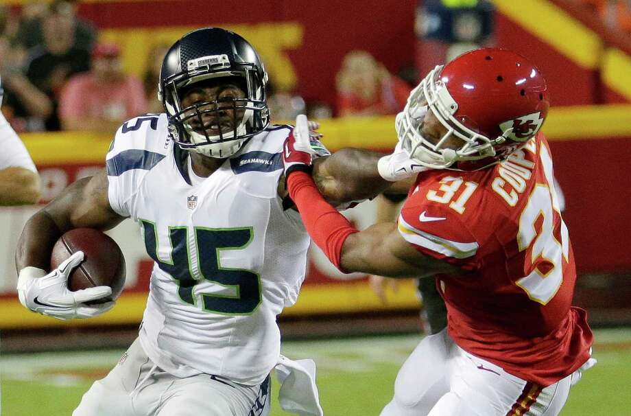 Seattle Seahawks running back Rod Smith (45) stiff-arms Kansas City Chiefs cornerback Marcus Cooper (31) during the second half of a preseason NFL football game at Arrowhead Stadium in Kansas City, Mo., Friday, Aug. 21, 2015. (AP Photo/Charlie Riedel) Photo: Charlie Riedel, Associated Press / AP