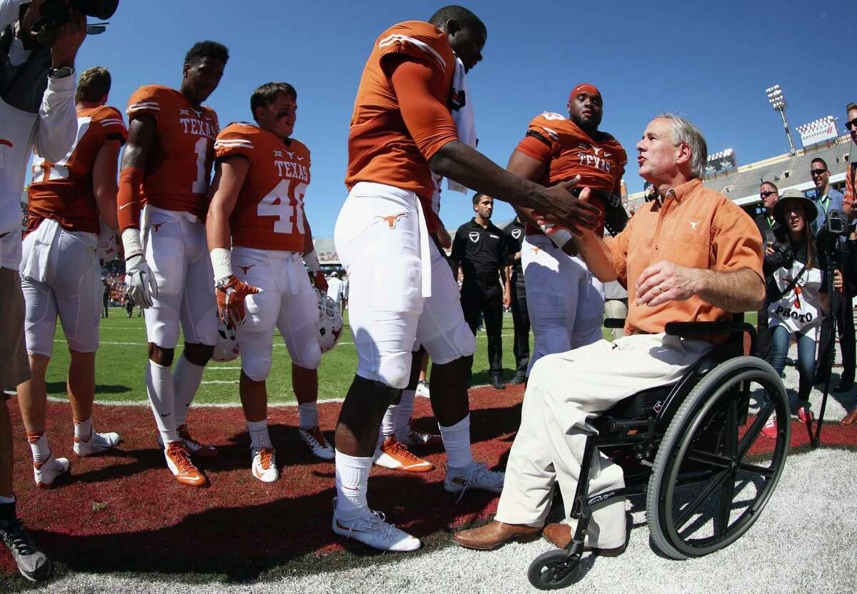 DALLAS, TX - OCTOBER 10: Texas Govenor Greg Abbott celebrates with the Texas Longhorns after they beat the Oklahoma Sooners 24-17 during the AT&T Red River Showdown at the Cotton Bowl on October 10, 2015 in Dallas, Texas.
