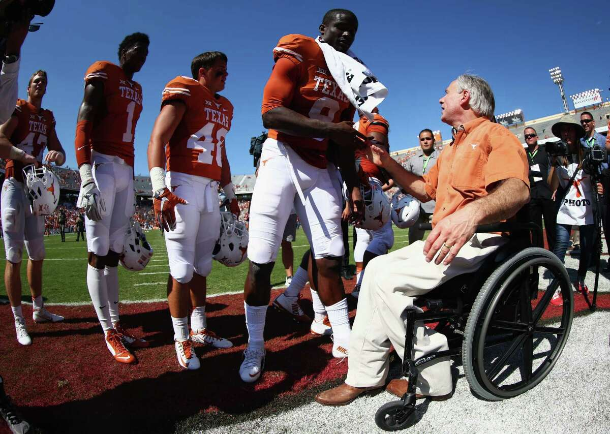 Texas Govenor Greg Abbott celebrates with the Texas Longhorns after they beat the Oklahoma Sooners 24-17 during the AT&T Red River Showdown at the Cotton Bowl on October 10, 2015 in Dallas.