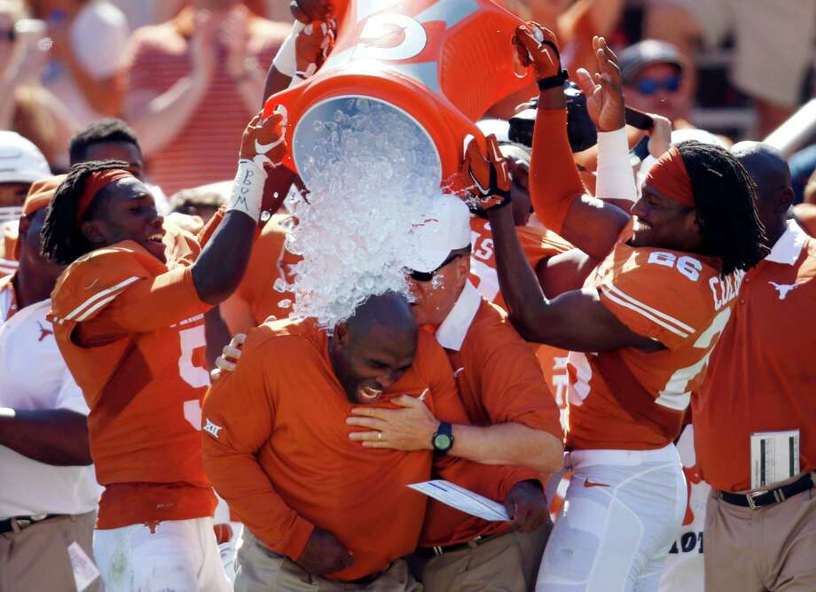 "Charlie Strong is doused in water by his players at the end of an uplifting victory at the Cotton Bowl that improved UT's record to 2-4 overall and 1-2 in the Big 12. ""We needed this,"" he said. Photo: Roger Steinman / Associated Press / FR171255 AP"