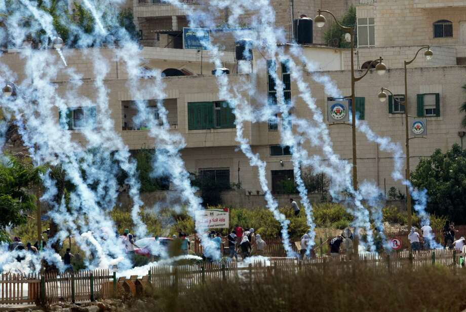 Palestinians run from tear gas fired by Israeli troops during clashes near Ramallah, West Bank, Saturday, Oct. 10, 2015. Palestinians carried out two stabbing attacks in Jerusalem on Saturday before being shot dead by police, the latest in a series of stabbing attacks against civilians and soldiers that have spread across Israel and the West Bank in the past week. The violence, including the first apparent revenge attack by an Israeli Friday and increasing protests by Israel's own Arab minority, has raised fears of the unrest spiraling further out of control. (AP Photo/Majdi Mohammed) Photo: Majdi Mohammed, STR / AP