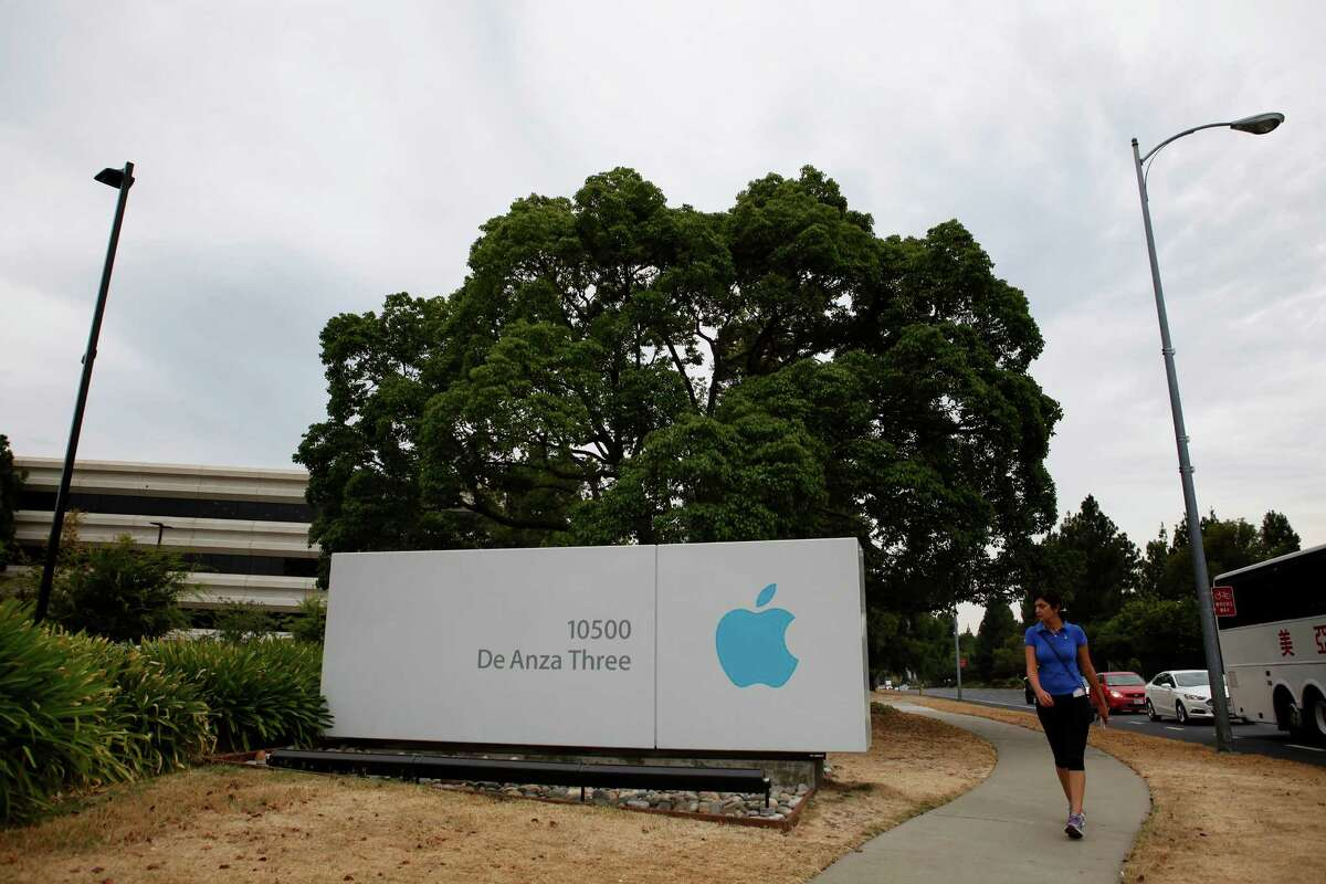 Farida Asadi, 26, walks along North De Anza Blvd. passing a large Apple sign in Cupertino, California, on Thursday, Aug. 6, 2015.
