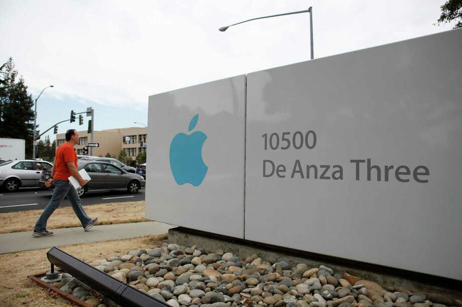 Pedestrians and cars pass by a large Apple sign on North De Anza Boulevard in Cupertino. Photo: Brandon Chew / Brandon Chew / The Chronicle / ONLINE_YES