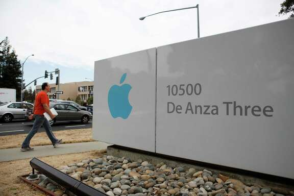 Pedestrians and cars pass by a large Apple sign on North De Anza Boulevard in Cupertino.