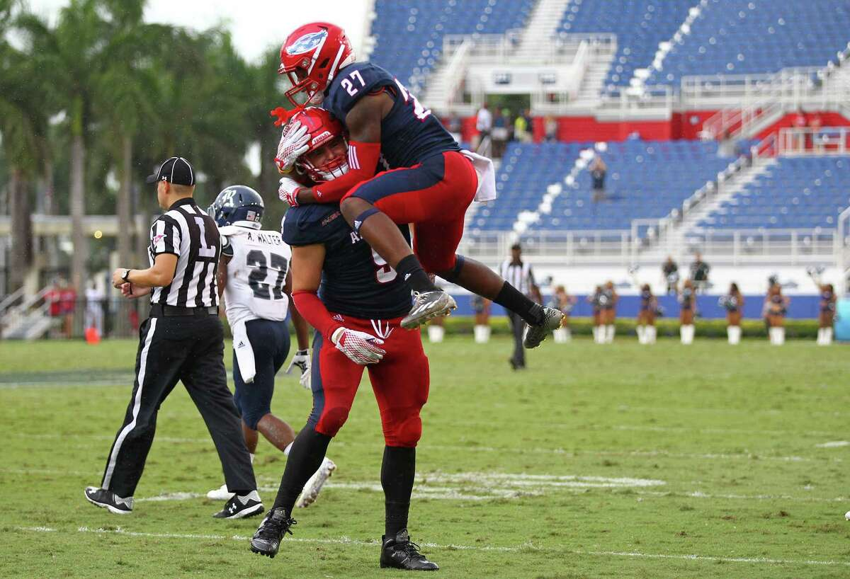 BOCA RATON, FL - OCTOBER 10: Andrew Soroh #27 of the Florida Atlantic Owls celebrates with Trey Hendrickson #9 after Hendrickson's sack of quarterback Driphus Jackson of the Rice Owls caused him to fumble the ball during the third quarter of the game at FAU Stadium on October 10, 2015 in Boca Raton, Florida.