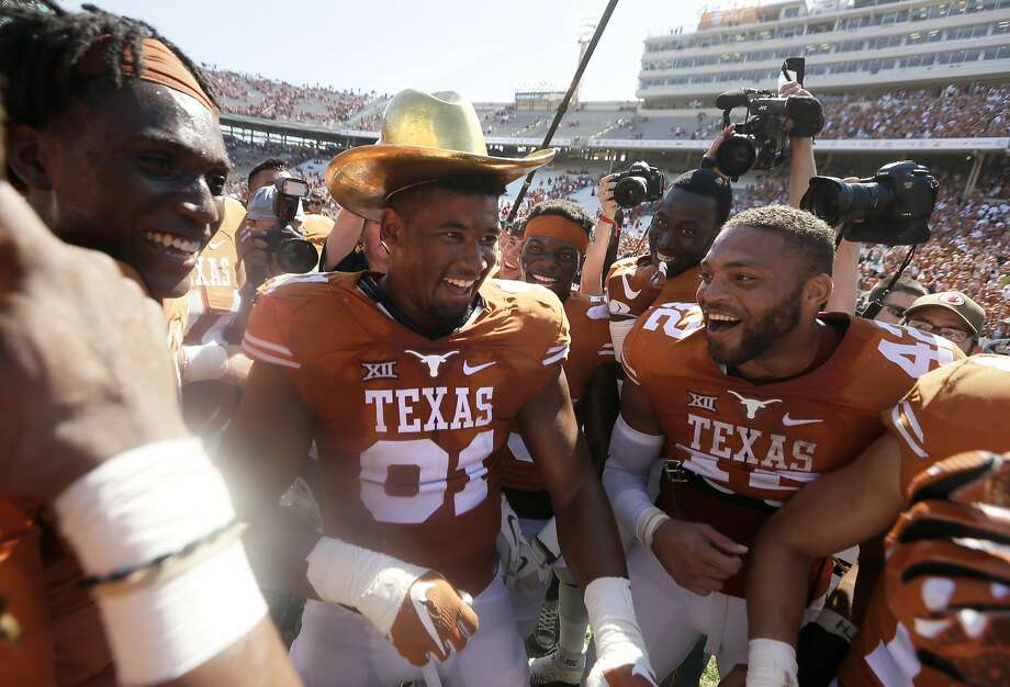 Texas defensive end Bryce Cottrell wears the traditional Golden Hat as he and his teammates celebrate an upset win over No. 10 Oklahoma at the Cotton Bowl in Dallas. Photo: LM Otero, Associated Press