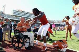 Texas Gov. Greg Abbott greets Malik Jefferson of the Texas Longhorns after a 24-17 win against the Oklahoma Sooners at the Cotton Bowl on Oct. 10, 2015 in Dallas