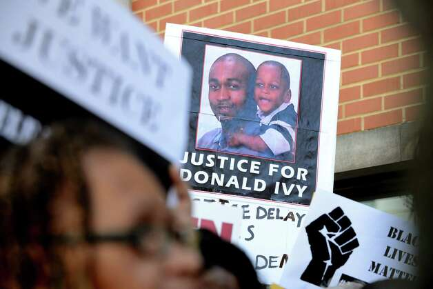 "Demonstrators hold signs in support of Marquis Dixon and ""Dontay"" Ivy during a press conference and rally outside Albany District Attorney David Soares' office Monday, Aug. 10, 2015, in Albany, N.Y.  (Will Waldron/Times Union) ORG XMIT: MER2015081015344385 Photo: WILL WALDRON / 00032956A"