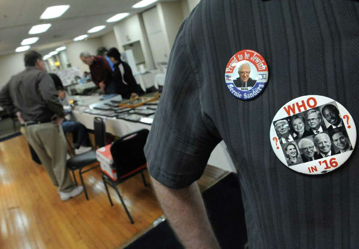 Dealer Adam Fine wears political pins he designed during the american political items collectors show at the Ramada Plaza on Saturday Oct. 10, 2015 in Albany, N.Y. (Michael P. Farrell/Times Union)