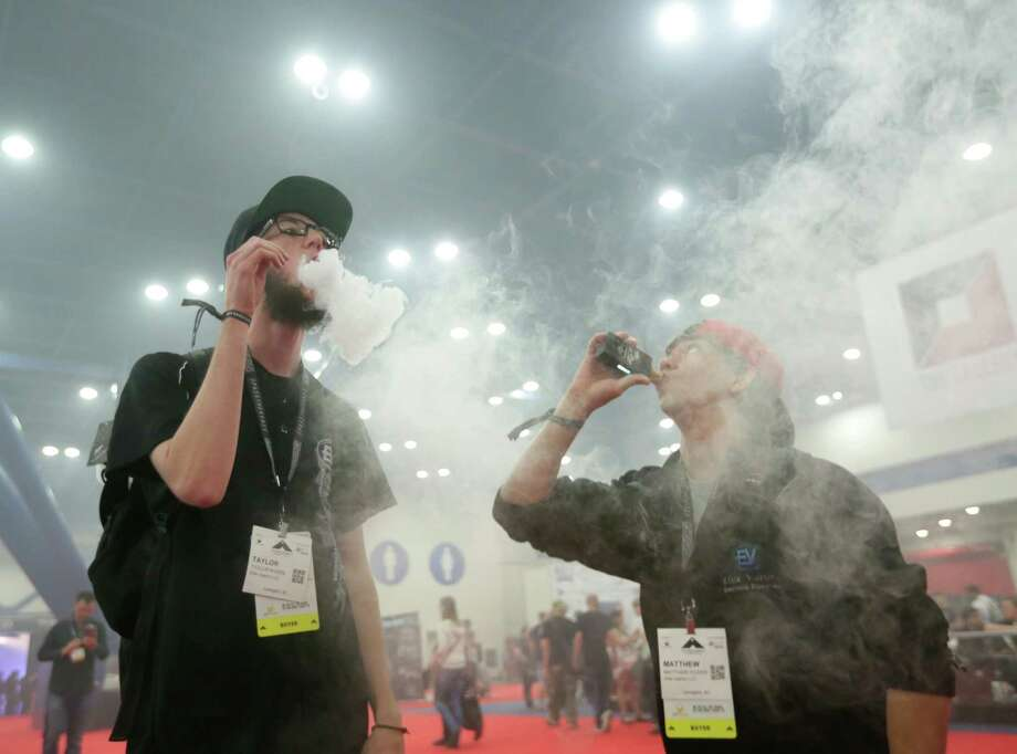 Taylor Rivers, left, and Matthew Dozier, blow large clouds Saturday during the Vape Summit IV at the George R. Brown Convention Center. Both men said they used to smoke cigarettes. Photo: Jon Shapley, Staff / © 2015  Houston Chronicle