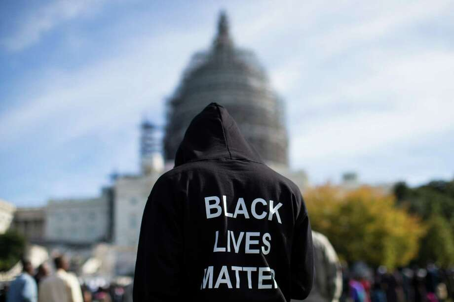 Neal Blair, of Augusta, Ga., stands on the lawn of the Capitol building during a rally to mark the 20th anniversary of the Million Man March, on Capitol Hill, on Saturday, Oct. 10, 2015, in Washington. Thousands of African-Americans crowded on the National Mall Saturday for the 20th anniversary of the Million Man March.  (AP Photo/Evan Vucci) Photo: Evan Vucci, STF / AP