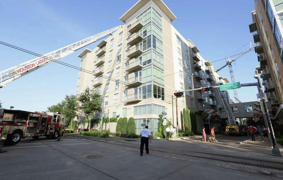 About 70 Houston firefighters work the scene of a two-alarm fire at the Venue Museum District apartments Saturday in Houston. No injuries were reported, and the fire was contained to one unit on the seventh floor, according to District Chief John Miller. Photo: Jon Shapley, Staff / © 2015  Houston Chronicle