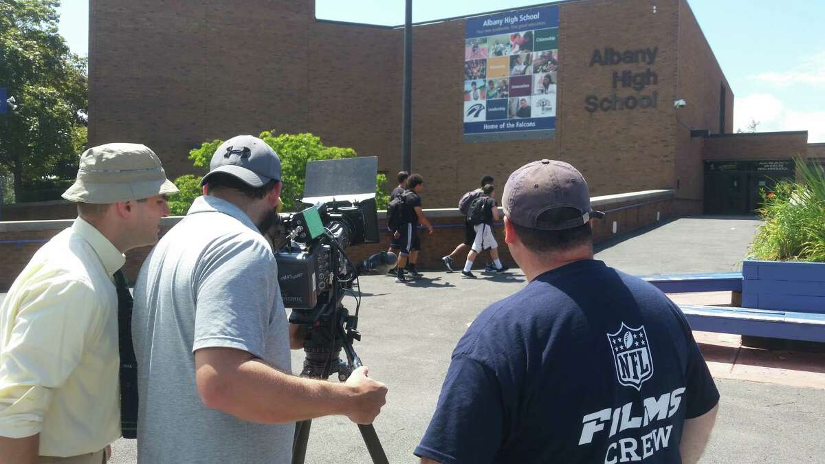 Members of an NFL Films crew shoot scene shots outside of Albany High School in July 2015 for a feature on former Albany High football legend Charlie Leigh. Paul Camarata, the film's producer and a Guilderland native, is at the left. (NFL Films photo)