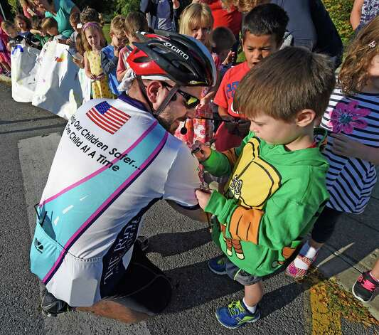 Matt Frear, left,  who's brother Craig Frear is missing gets an autograph from student Frankie Ruscitto as the Ride for Missing Children makes a stop at Birchwood Elementary School Friday morning Sept. 19, 2015 in Niskayuna, N.Y.     (Skip Dickstein/Times Union) Photo: SKIP DICKSTEIN / 00033390A
