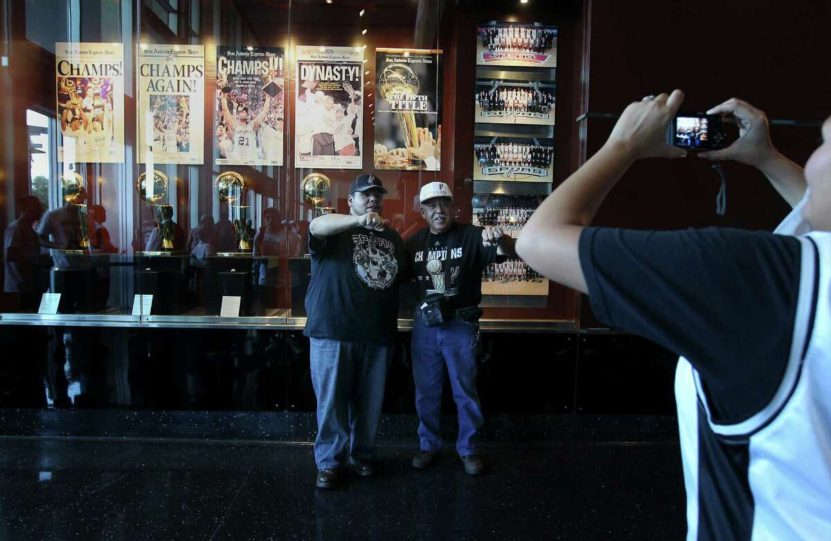 Christopher Tristan (left) and his father Luis pose for a picture with their replica Spurs Championship rings before the start of the Spurs and Dallas Mavericks season opener at the AT&T Center on Tuesday, Oct. 28, 2014. (Kin Man Hui/San Antonio Express-News)