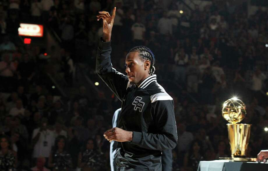 Spurs' Kawhi Leonard (02) acknowledges the crowd after receiving his 2014 NBA Championship ring during the ring ceremony and season opener against the Dallas Mavericks at the AT&T Center on Tuesday, Oct. 28, 2014. (Kin Man Hui/San Antonio Express-News) Photo: Kin Man Hui, Staff / San Antonio Express-News / ©2014 San Antonio Express-News