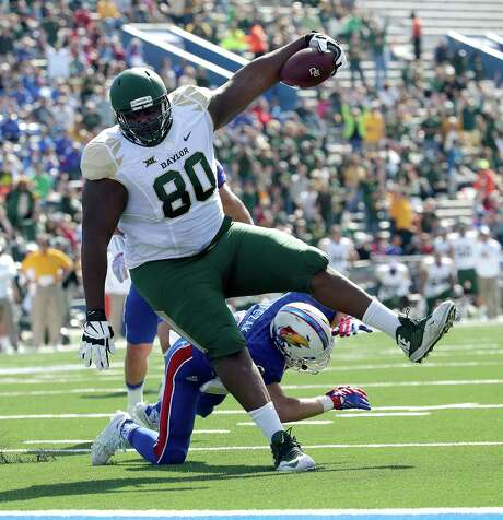Baylor's 410-pound LaQuan McGowan gets in on the fun by rambling past Kansas' 173-pound Michael Glatczak on a touchdown reception in the first half. Photo: Charlie Riedel, STF / AP