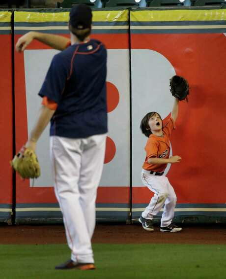 Since he's not on the Astros' ALDS roster, reliever Chad Qualls has some spare time to play catch with son Caiden, 6, on Saturday at Minute Maid Park. Photo: Melissa Phillip, Staff / © 2015 Houston Chronicle
