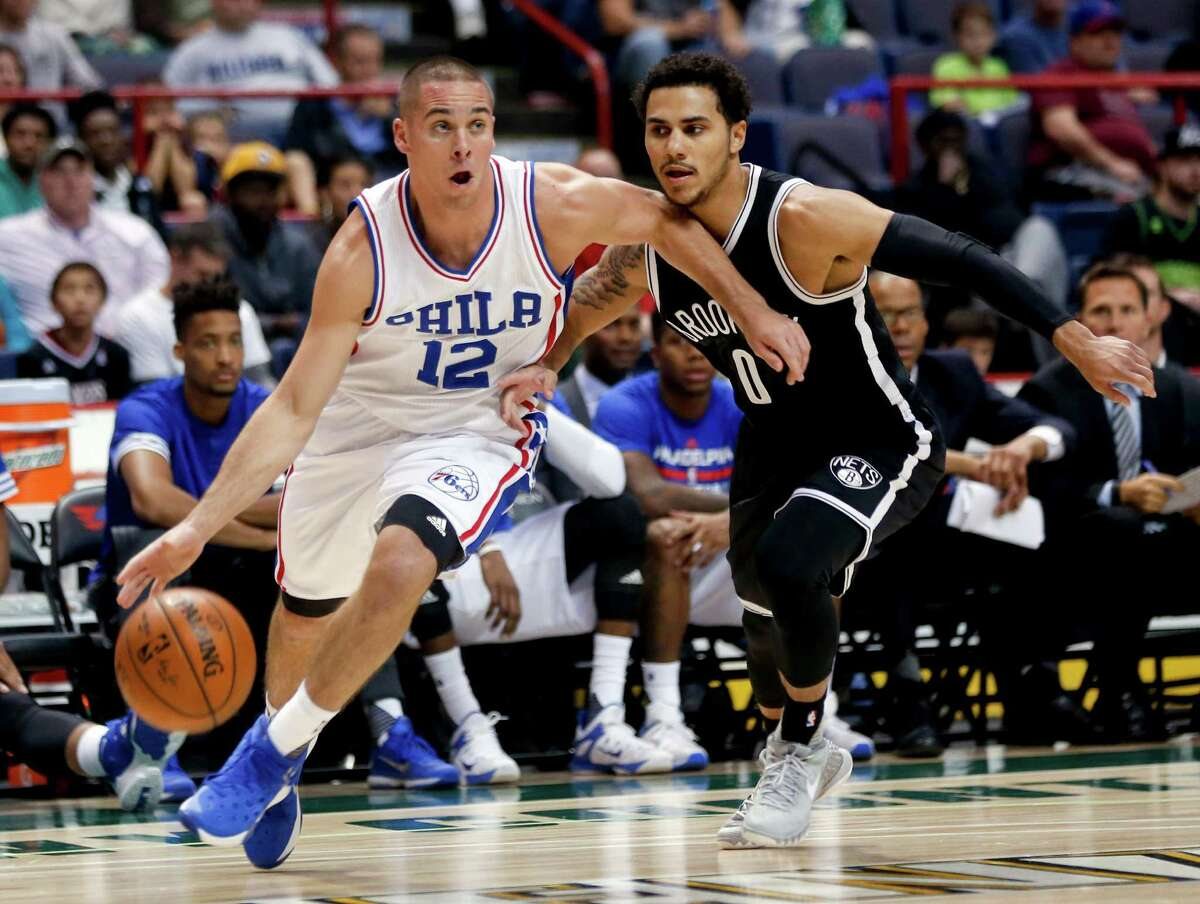 Philadelphia 76ers guard T.J. McConnell (12) drives past Brooklyn Nets guard Shane Larkin (0) during the first half of an NBA preseason basketball game, Saturday, Oct. 10, 2015, in Albany, N.Y. (AP Photo/Mike Groll) ORG XMIT: NYMG104