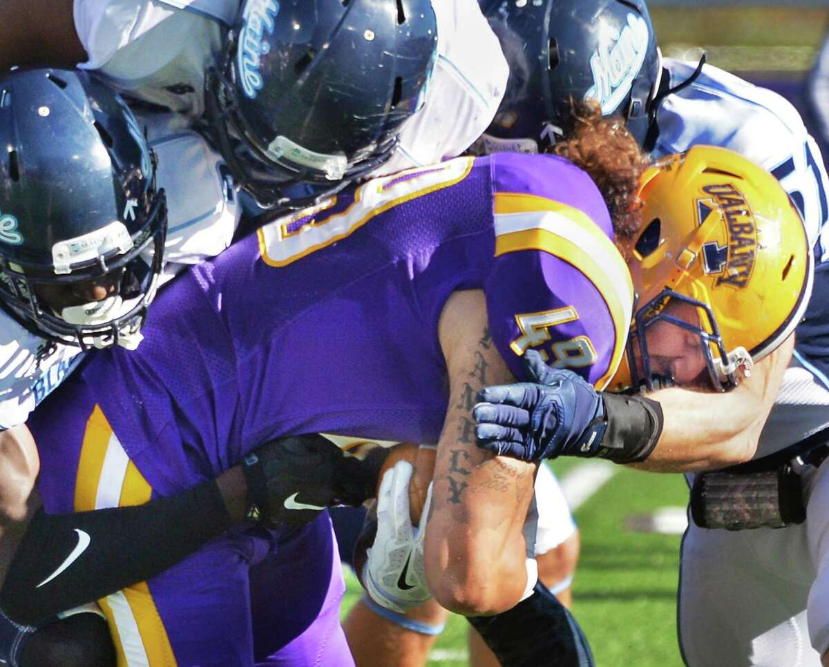 UAlbany's #49 Anthony Manzo-Lewis is brought down by a host of Maine defenders during Saturday's game at Casey Stadium Oct. 10, 2015 in Albany, NY. (John Carl D'Annibale / Times Union)