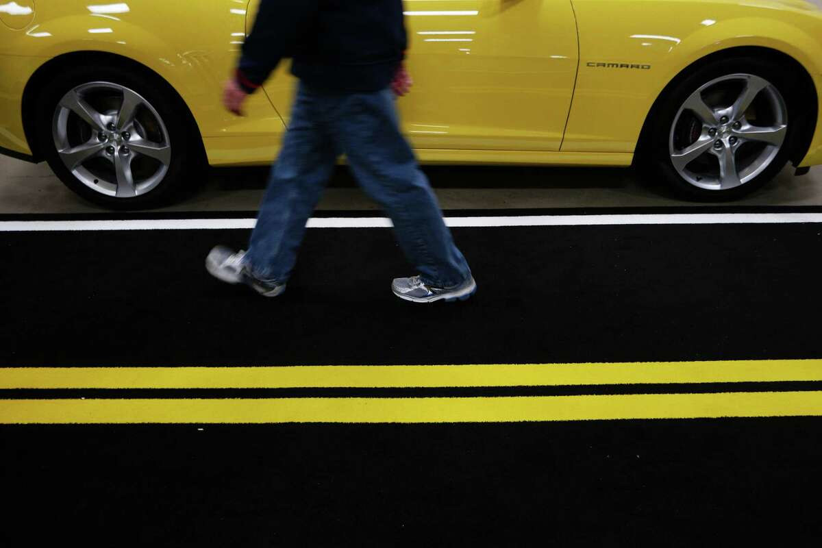 People walk past a Chevy Camaro SS during the Seattle Auto Show at CenturyLink Field Events Center. The Seattle Auto Show continues through October 11th. Photographed on Wednesday, October 10, 2015.