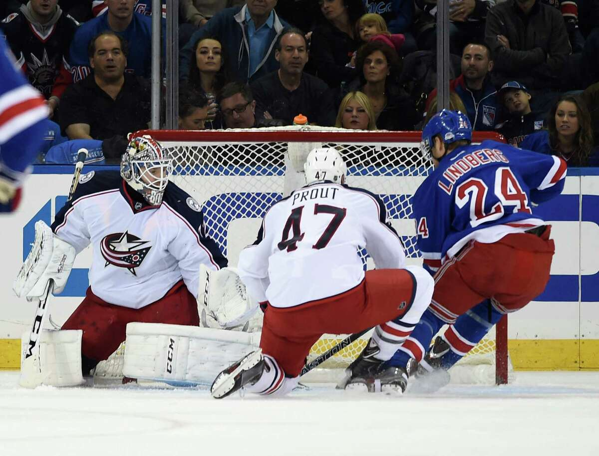 New York Rangers center Oscar Lindberg (24) shoots the puck past Columbus Blue Jackets defenseman Dalton Prout (47) and goalie Sergei Bobrovsky (72) to score his second goal during the first period of an NHL hockey game Saturday, Oct. 10, 2015, in New York. (AP Photo/Kathy Kmonicek) ORG XMIT: MSG103