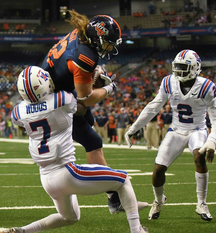 UTSA's David Morgan II hauls in a first-half touchdown pass as Louisiana Tech's Xavier Woods (7) and Secdrick Cooper (2) attempt to defend at the Alamodome on Oct. 10, 2015. Photo: Billy Calzada /San Antonio Express-News / San Antonio Express-News