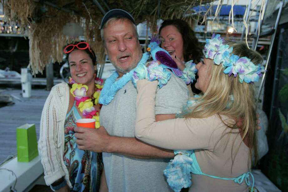 From left, Sarah Welch, Megan Bernard, both of Stamford and Maria Wardell of Old Greenwich, adjusts the fake parrot that Phil Varbero of Greenwich was wearing as part of his costume during a Pre-Columbus Day lighted boat party in Stamford Harbor's West Branch on Oct. 10, 2015. Photo: Matthew Brown / For Hearst Connecticut Media / Connecticut Post Freelance