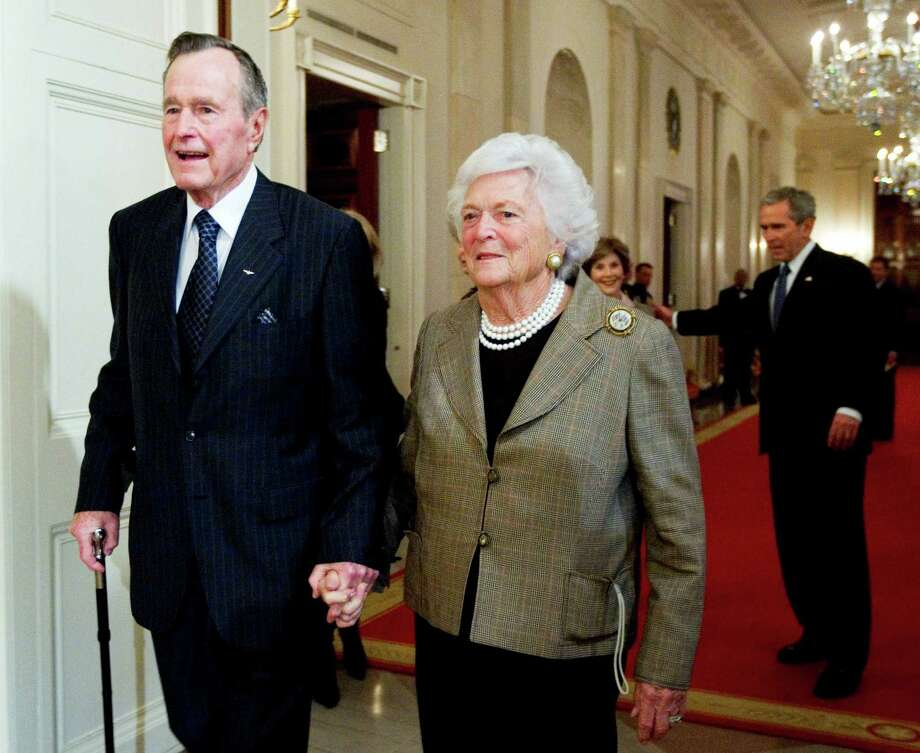 Former President George H. W. Bush, left, walks with his wife, former first lady Barbara Bush, followed by their son, President George W. Bush, and his wife first lady Laura Bush, to a reception in honor of the Points of Light Institute, Jan. 7, 2009, at the White House. Photo: Manuel Balce Ceneta, STF / AP