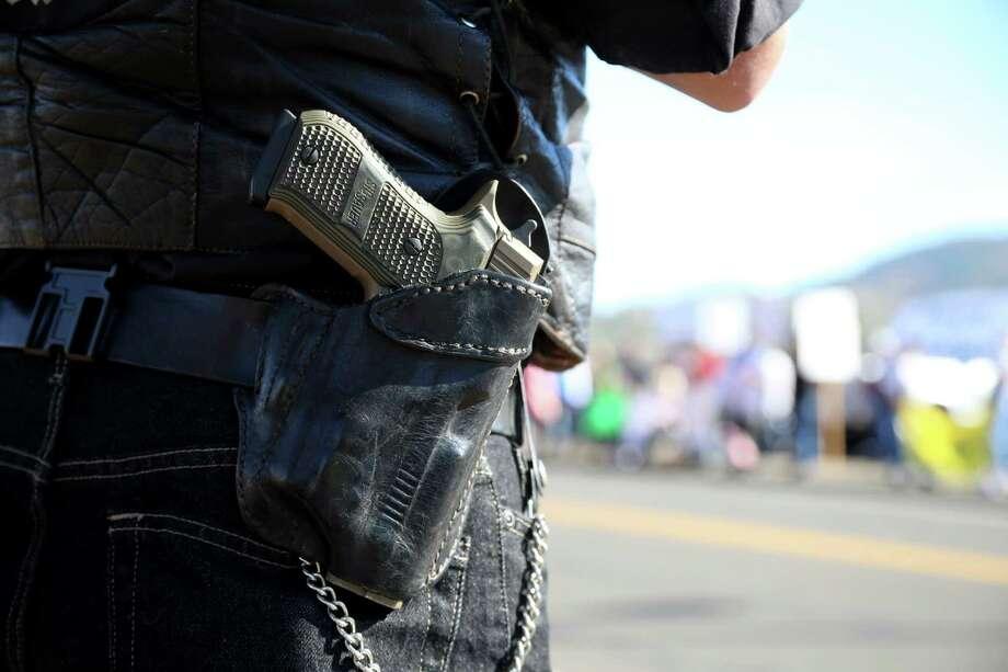 A demonstrator's handgun is seen as he waits outside of Roseburg Regional Airport for President Barack Obama's arrival in Roseburg, Ore. Photo: Ryan Kang, FRE / FR171219 AP