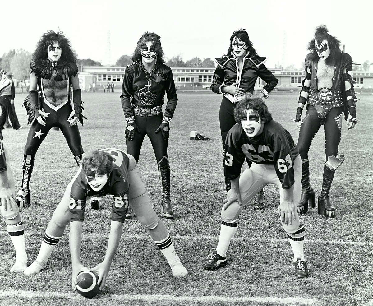 FILE-- In this Oct. 9, 1975 file photo, members of the rock band KISS, from top left: Paul Stanley, Peter Criss, Ace Frehley and Gene Simmons, line up behind two members of the Cadillac High School Vikings football team, wearing KISS facepaint, in Cadillac, Mich. The small northern Michigan city is celebrating the 40th anniversary of an unforgettable visit by rock 'n' roll band Kiss with two days of events and a monument dedicated to the band.