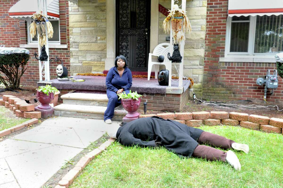 Jeannine Haddon poses on the porch of her Halloween decorated home, Friday, Oct. 9, 2015, in Detroit. The dummy placed face down in her front yard as a Halloween prank has prompted repeated visits by police. (Charles V. Tines/Detroit News via AP)