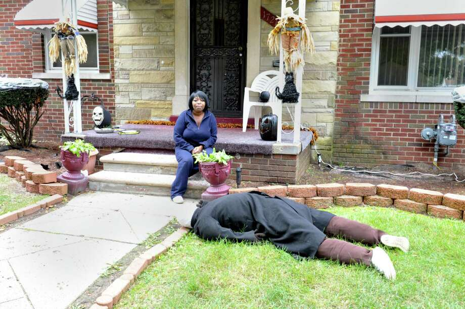 Jeannine Haddon poses on the porch of her Halloween decorated home, Friday, Oct. 9, 2015, in Detroit. The dummy placed face down in her front yard as a Halloween prank has prompted repeated visits by police. (Charles V. Tines/Detroit News via AP)  Photo: Charles V. Tines, AP / Detroit News
